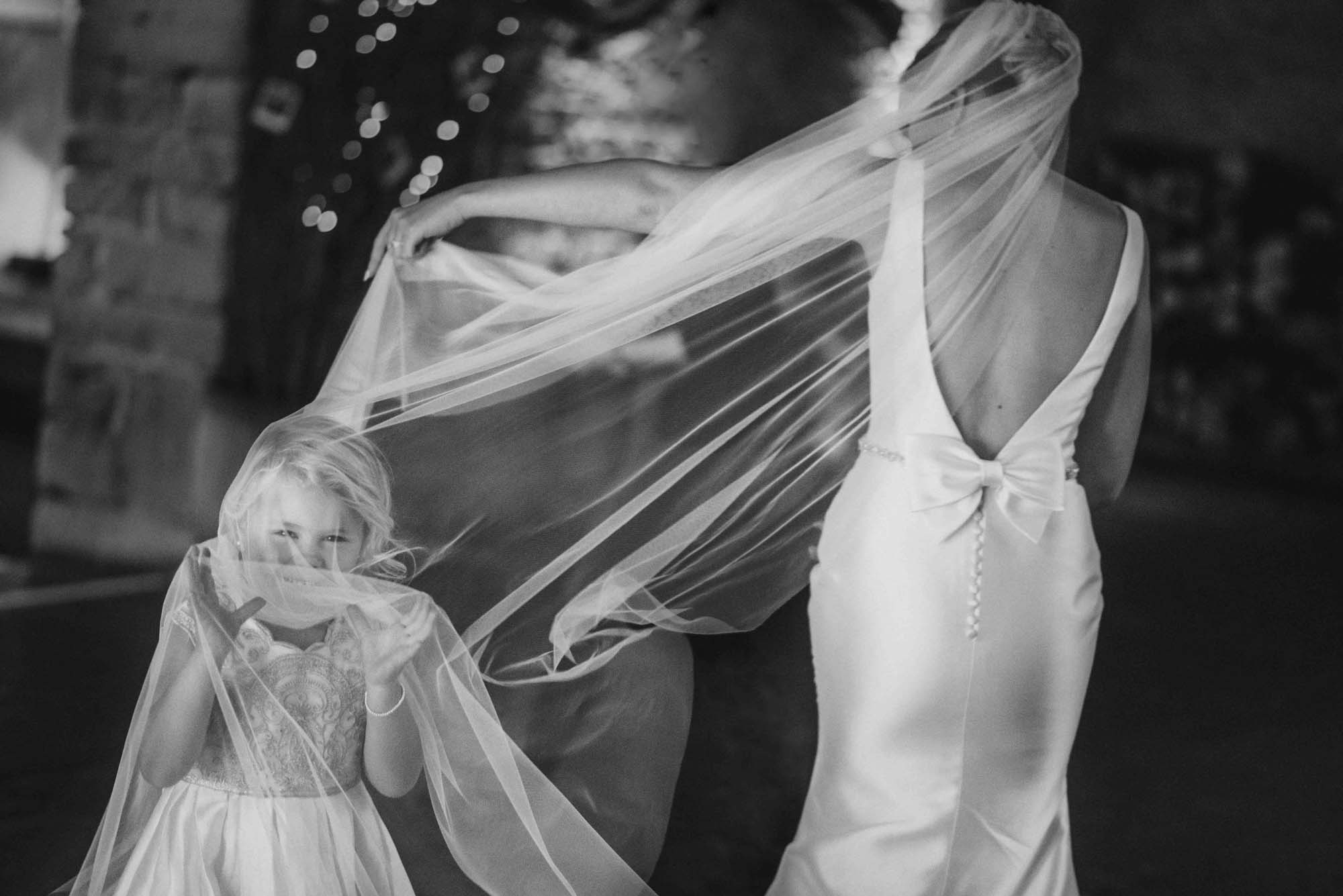 Flower girl playing in Bride Veil Photo
